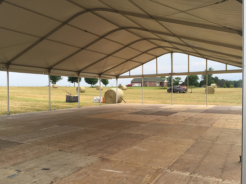 Tent manufacturers setting up venue for outdoor event.